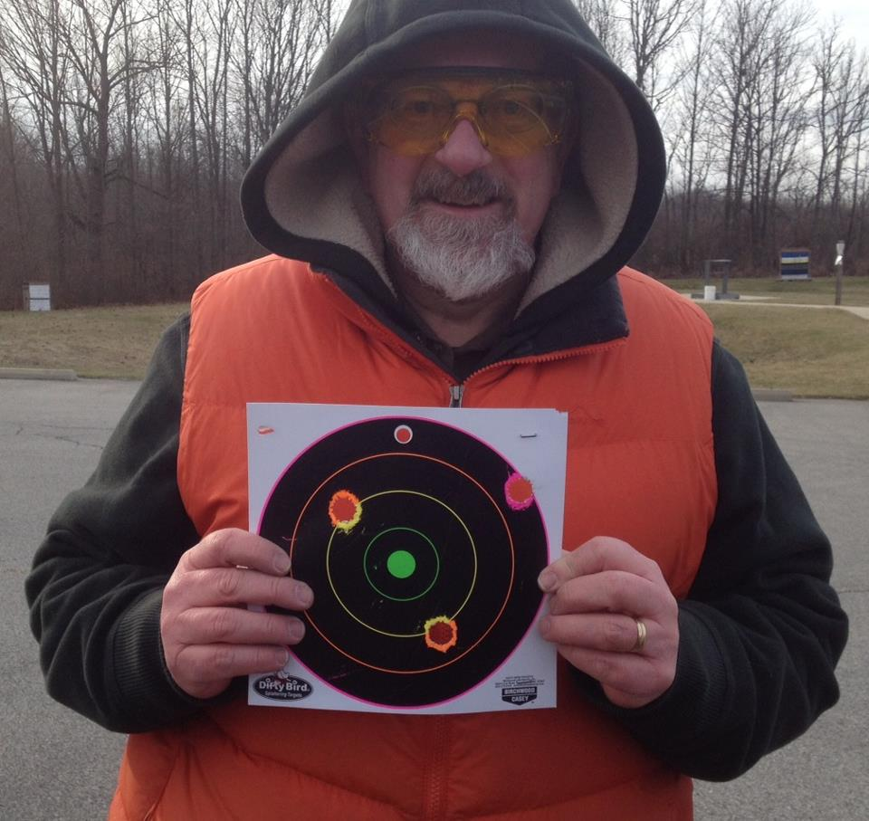 Me, shivering, with the target I used for shooting 12 gauge shotgun slugs at 50 yards. Those are really big holes. Three out of five on the target--I'm happy with that.