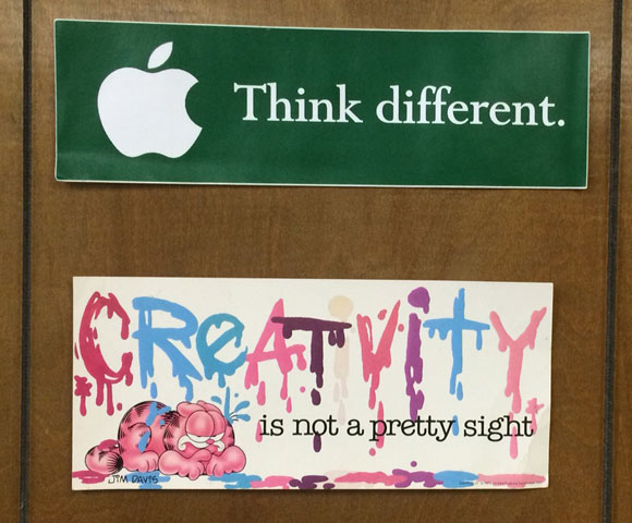 Two bumper stickers on the 1970s-era wood paneling in my office.